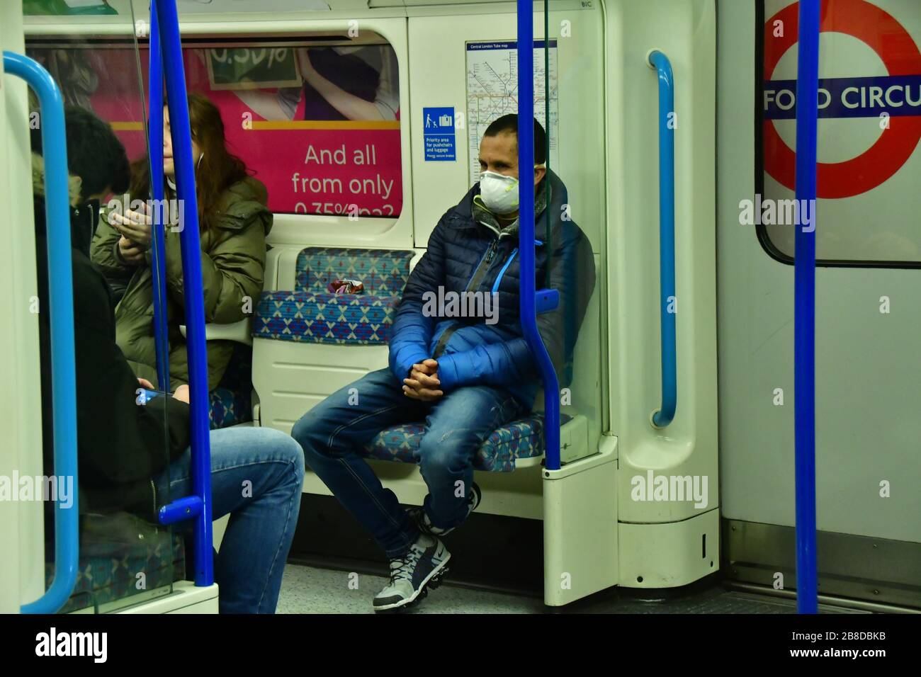 London, UK. 21st March 2020. A beggar without mask begging at Oxford Circus underground people sitting inside the tube wearing mask on 21 March 2020, UK. Credit: Picture Capital/Alamy Live News Stock Photo