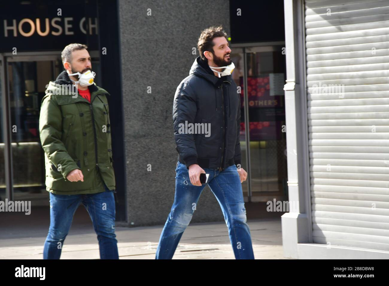 London, UK. 21st March 2020. A couple of guyus take off the wearing a mask at street during Coronavirus - Pandemic hit Oxford Street many shops closure a few open but empty on 21 March 2020, UK. Credit: Picture Capital/Alamy Live News Credit: Picture Capital/Alamy Live News Stock Photo