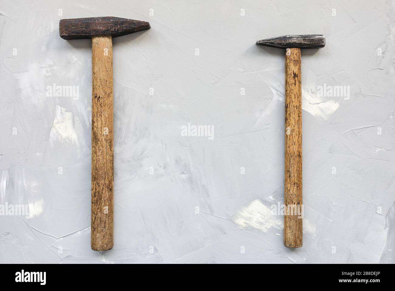Two old rusty hammers on gray background, carpentry concept, copy space Stock Photo