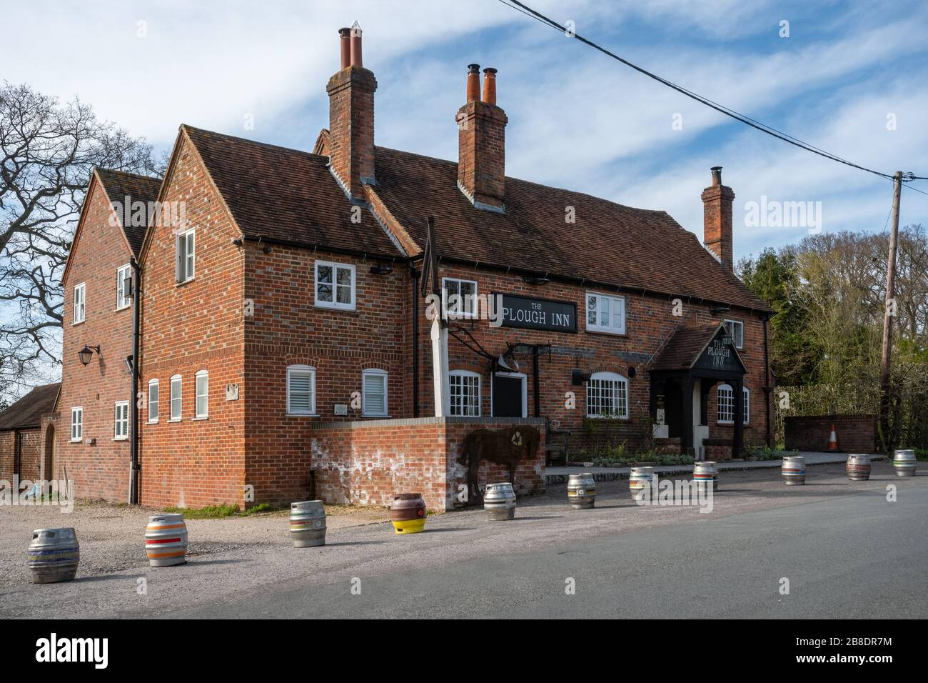 English pub closed due to the covid-19 coronavirus pandemic, with beer kegs lined up in front. The Plough Inn, village of Little London, Hampshire, UK Stock Photo