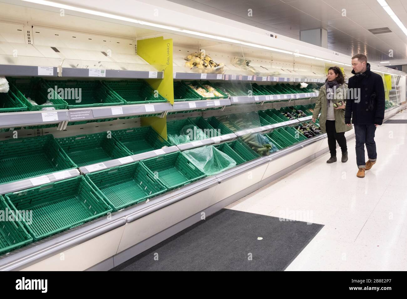 London, UK. 21st Mar, 2020. People walk by almost-empty shelves of a supermarket in London, Britain, March 21, 2020. As of 9a.m. (0900GMT) on Saturday, 72,818 people have been tested in Britain, of which 67,800 were confirmed negative and 5,018 were confirmed positive. 233 patients in the country who tested positive for the virus have died. Credit: Xinhua/Alamy Live News Stock Photo