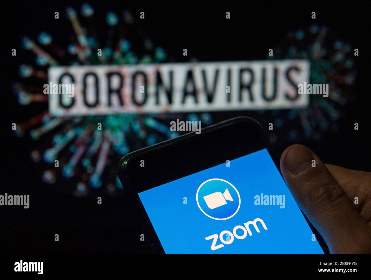 In this photo illustration the American video Communications company Zoom  logo seen displayed on a smartphone with a computer model of the COVID-19 coronavirus on the background. Stock Photo