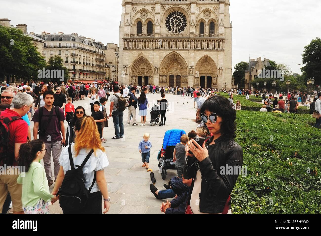 A long line of tourists waiting to enter the Cathédrale Notre-Dame de Paris and a woman checking here phone, Parvis Notre-Dame - Pl. Jean-Paul II. Stock Photo