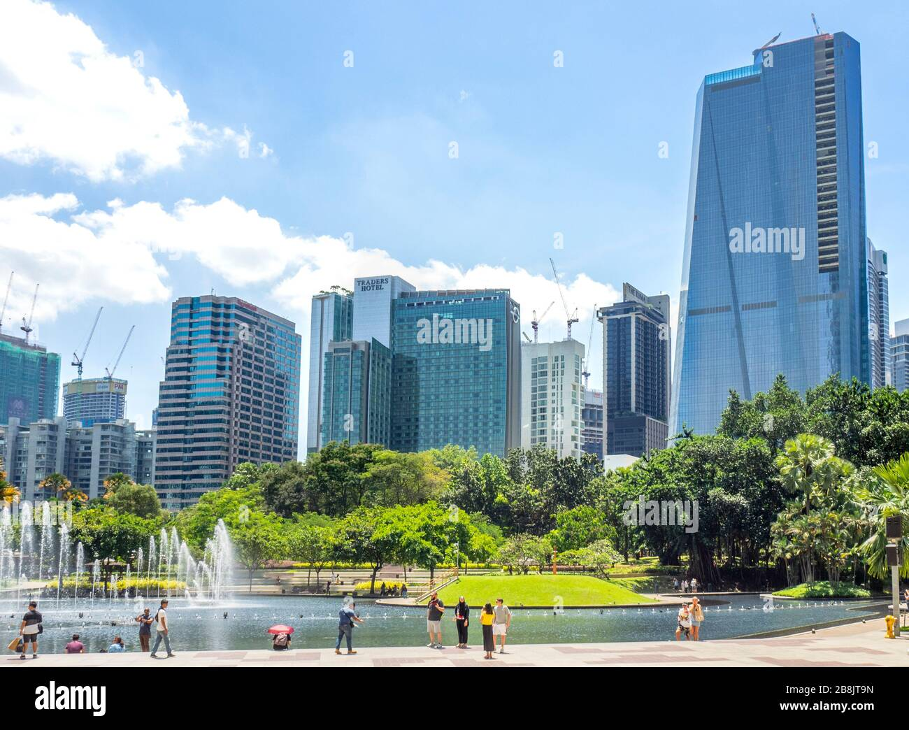 Office and residential high rise towers and fountains in Symphony Lake and tourists enjoying a day at KLCC Park Kuala Lumpur Malaysia. Stock Photo