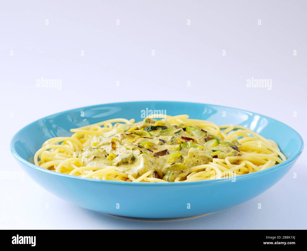 Spaghetti with a cream sauce with zucchini and leek  in a light blue plate on a white background. Stock Photo