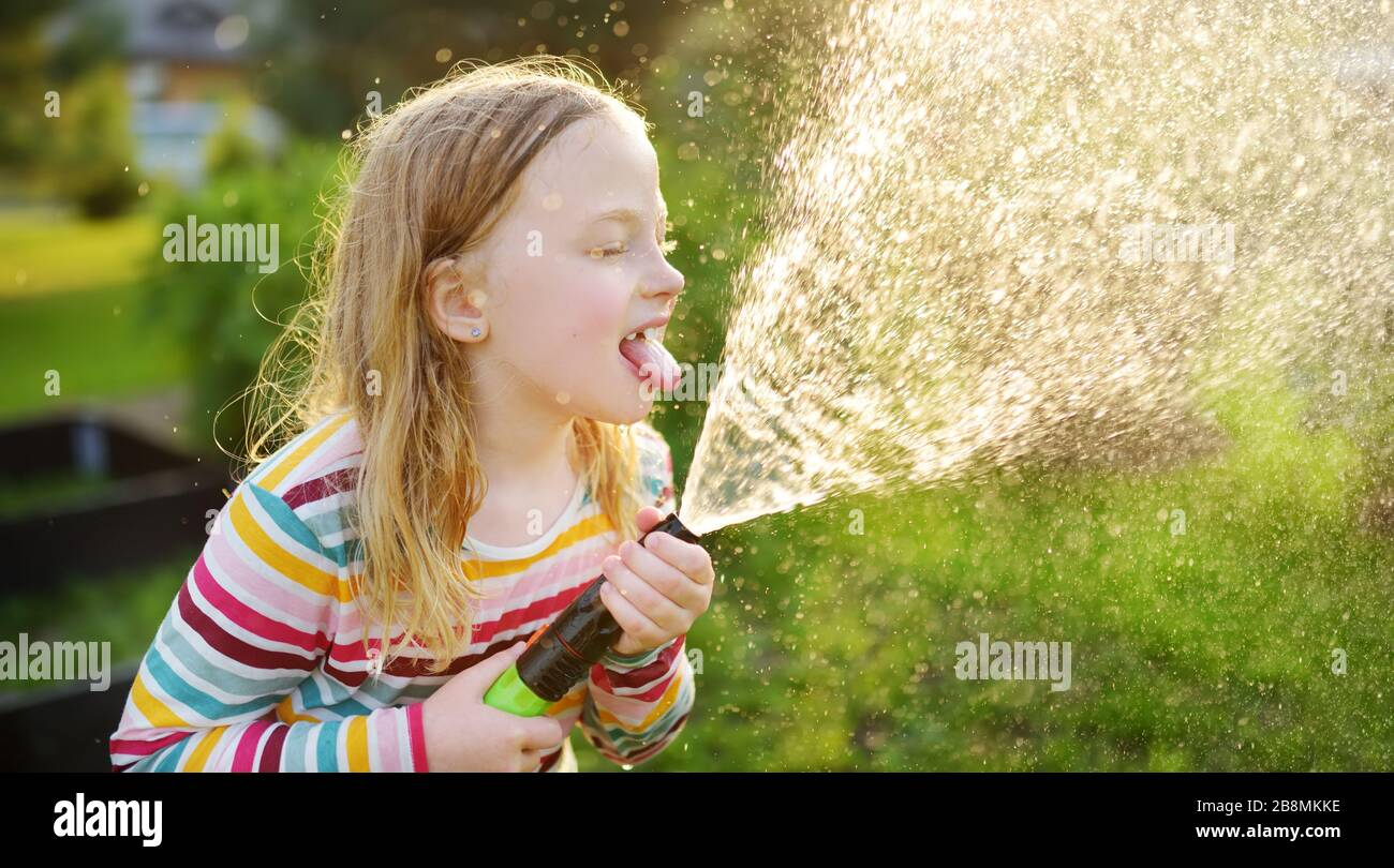 Adorable little girl playing with a garden hose on warm summer day