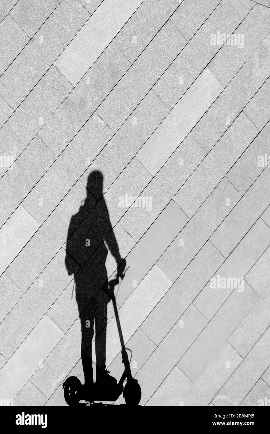 Shadow silhouette of a person riding electric scooter on empty city sidewalk pavement, in black and white Stock Photo