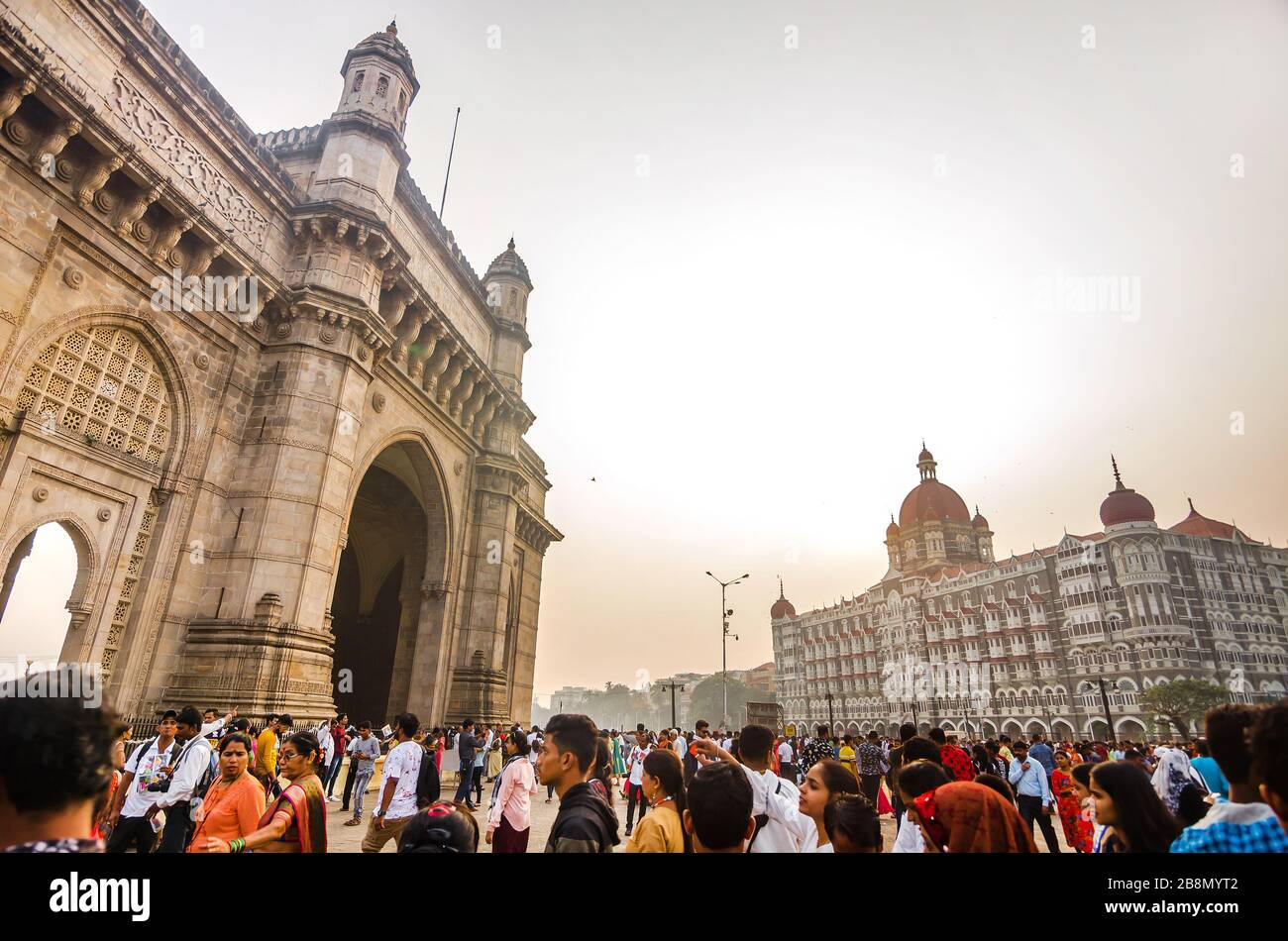 MUMBAI, INDIA – DEC. 8, 2019: Visitors enjoying near Gateway of India, opposite to the prime tourist attraction Taj Mahal Palace and Tower Hotel. Stock Photo