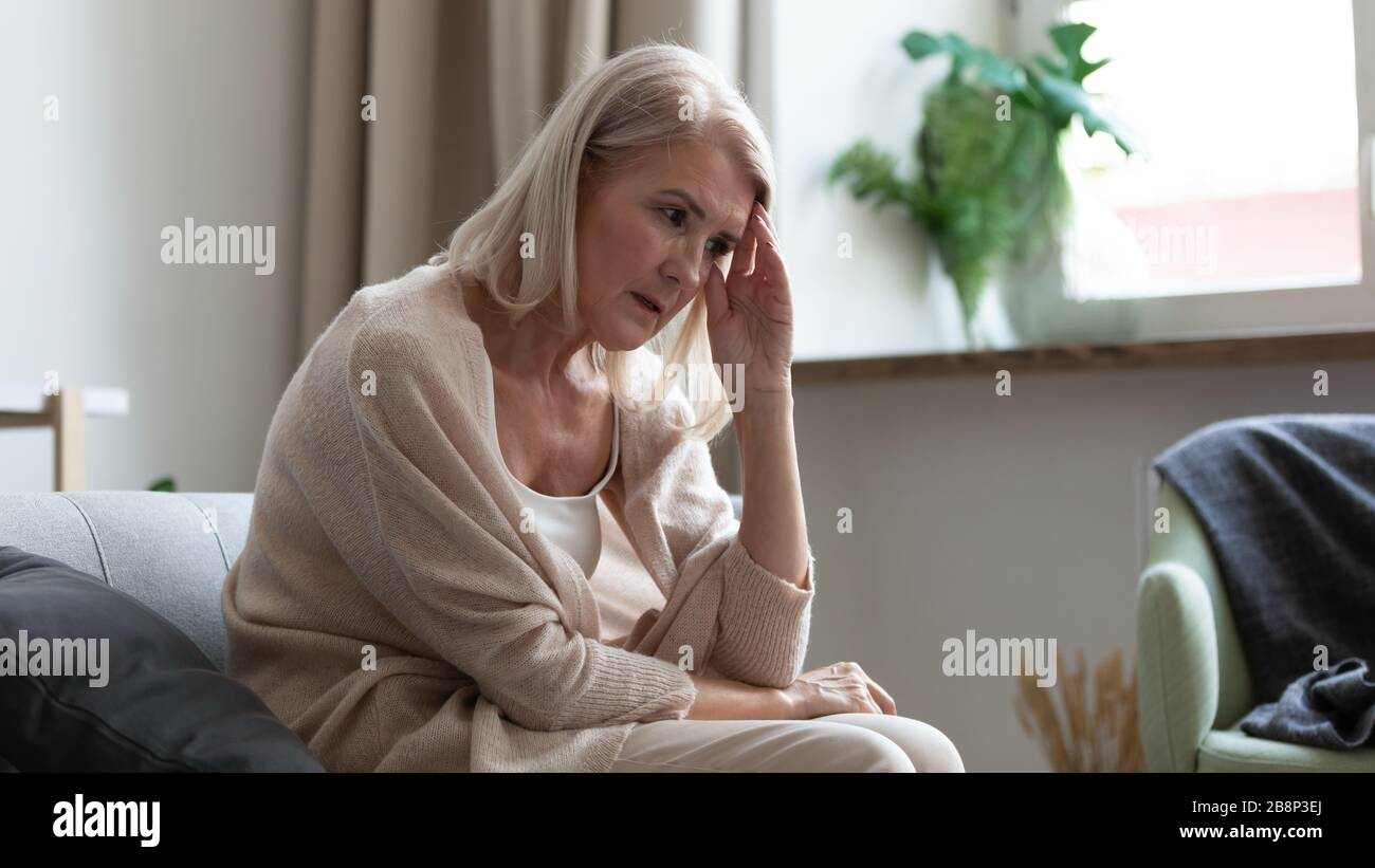 Stressed upset mature woman thinking of personal troubles. Stock Photo