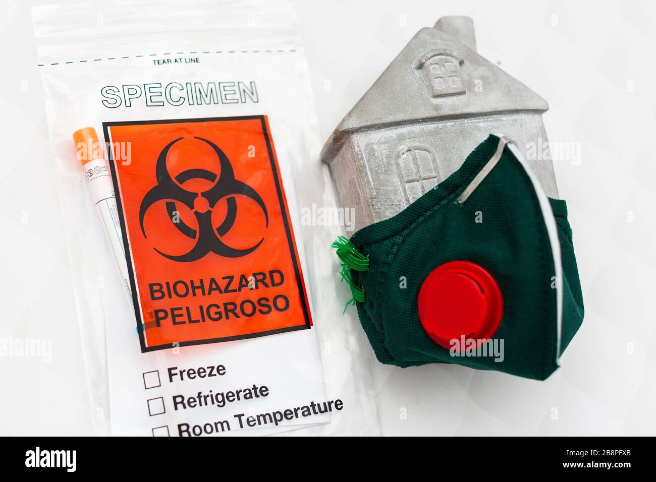 concept of an appeal to stay at home. Respiratory mask on a toy house and a virus test. Stock Photo