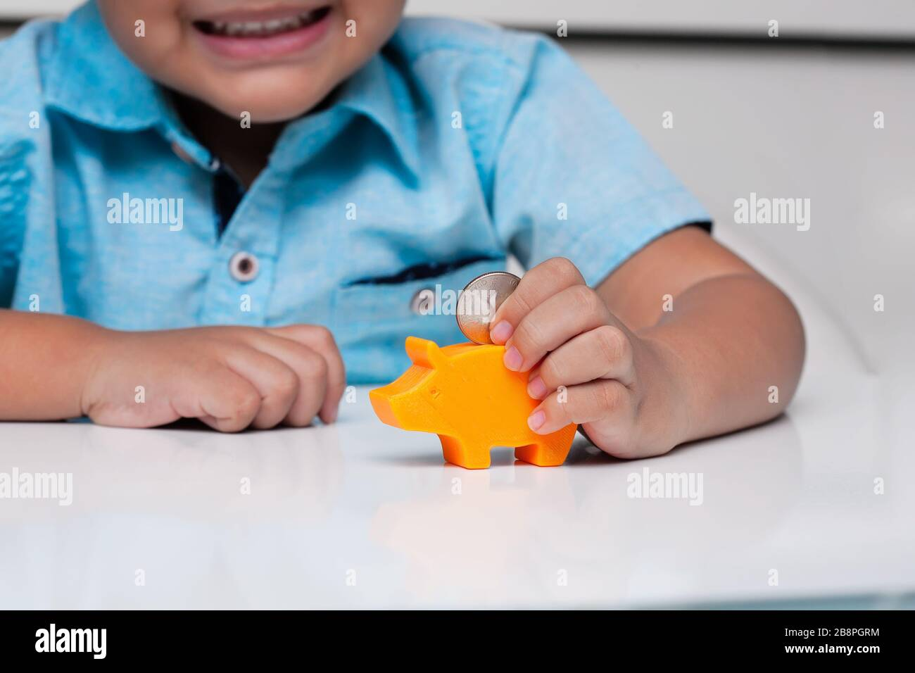 A young boy demonstrating fine motor skills by using a pincer grasp to hold a coin, before putting it into a small piggy bank slot. Stock Photo