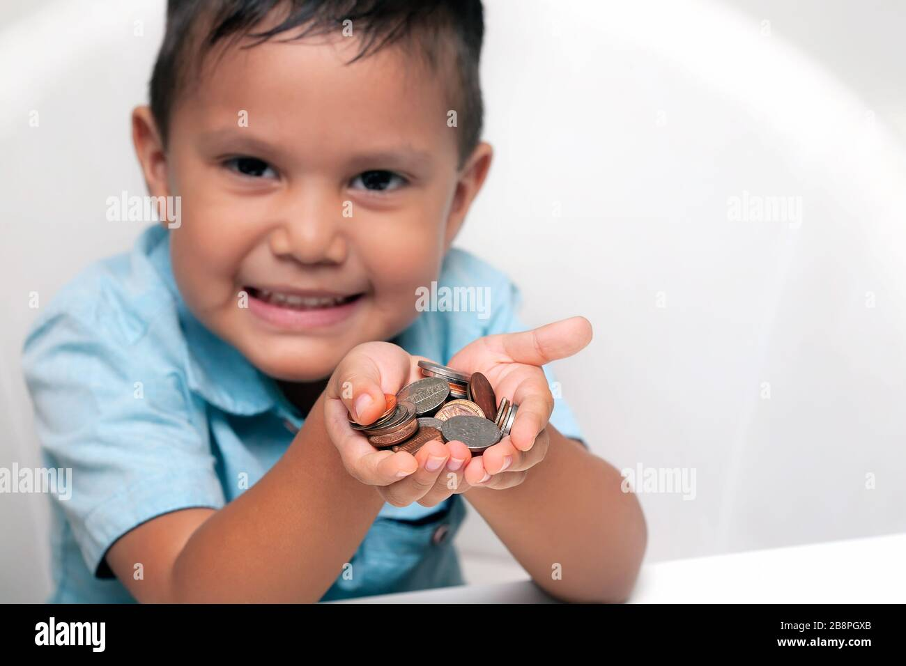 A Hispanic toddler holding U.S. coins in his cupped hands, with a friendly smile to suggest giving or donating money. Stock Photo
