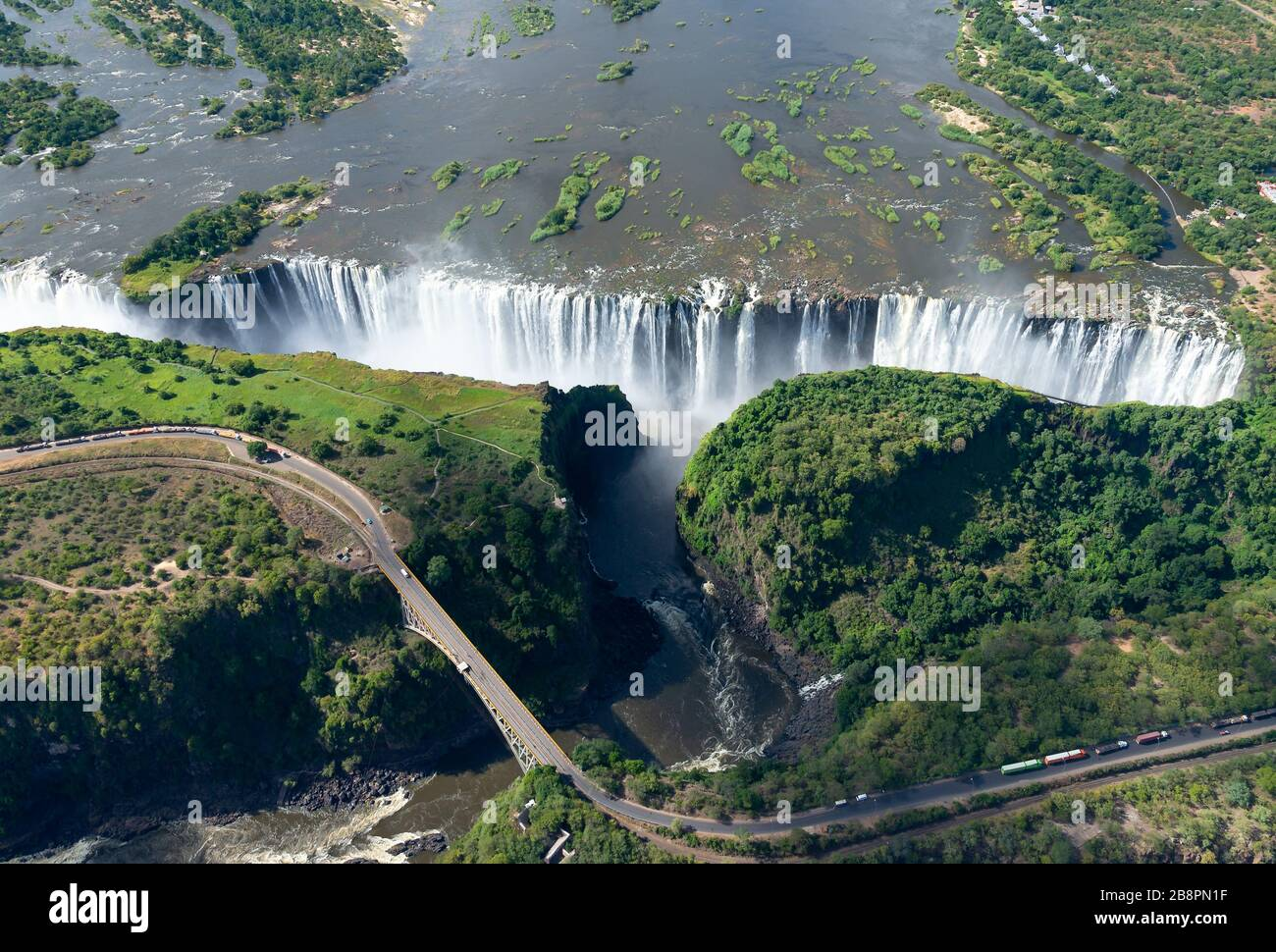 Aerial view of Victoria Falls located between Zimbabwe and Zambia in Africa. Seven Natural Wonders of the World. Zambezi River and border bridge. Stock Photo
