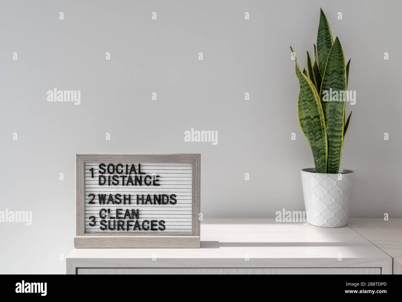 COVID-19 Coronavirus health safety guidelines. Text board in public space with rules, practice social distancing, wash hands often, clean surfaces Stock Photo
