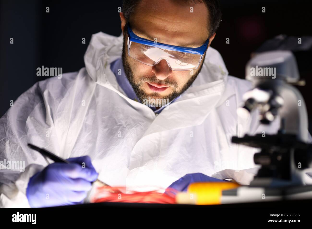 Man laboratory repairs instrument near microscope Stock Photo