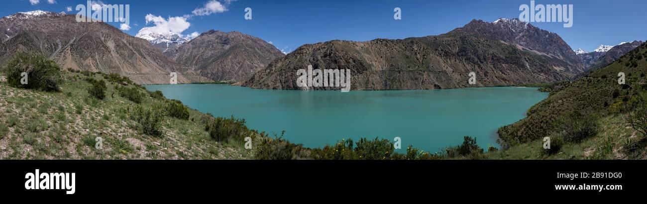 Panorama of the blue green Iskanderkul lake in Tadzjikistan with high snowy mountains. Stock Photo