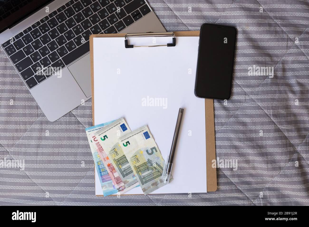 Blank notebook with pencil, cell phone and euro money on bed. Unemployment. Cash crunch. Lack of money. Job seeker.  Stock Photo