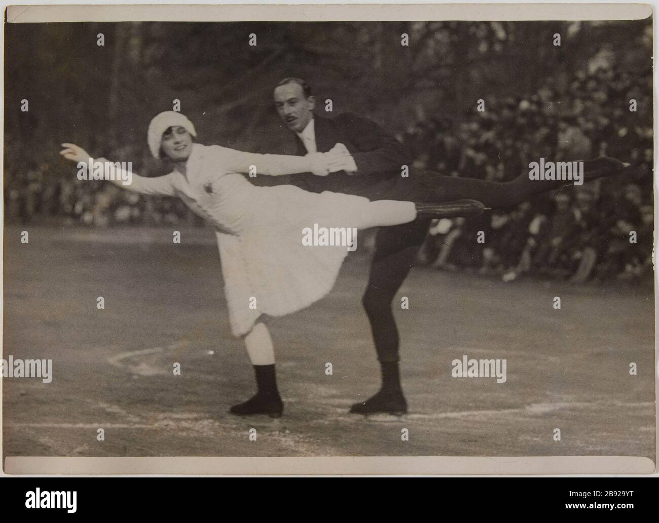 "Bois de Boulogne / Mr. Brunet and Ms. Joly. Mr. Brunet and Ms. Joly, world champion figure skating a figure running, Bois de Boulogne, 16th arrondissement, Paris. ""Monsieur Brunet et Mademoiselle Joly, champion du monde de patinage artistique exécutant une figure. Bois de Boulogne, Paris (XVIème arr.)"". Photographie de Georges Devred pour l'agence Rol. 17 février 1929. Paris, musée Carnavalet. Stock Photo"