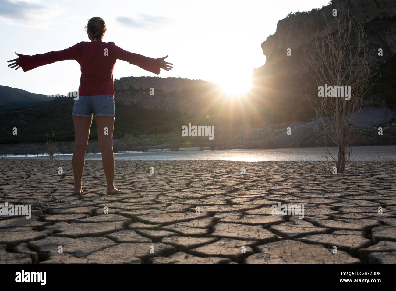 Backlit woman at the edge of a lake with her arms outstretched. Stock Photo