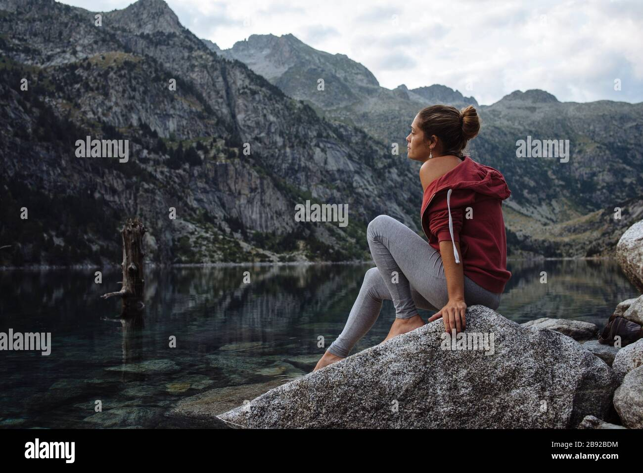 Woman with bun sitting on a rock by a lake during a trip. Stock Photo