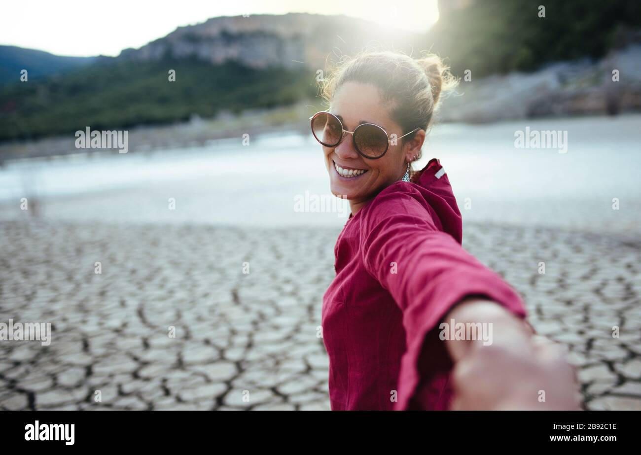 Smiling woman holding her hand for her boyfriend looking at the camera Stock Photo