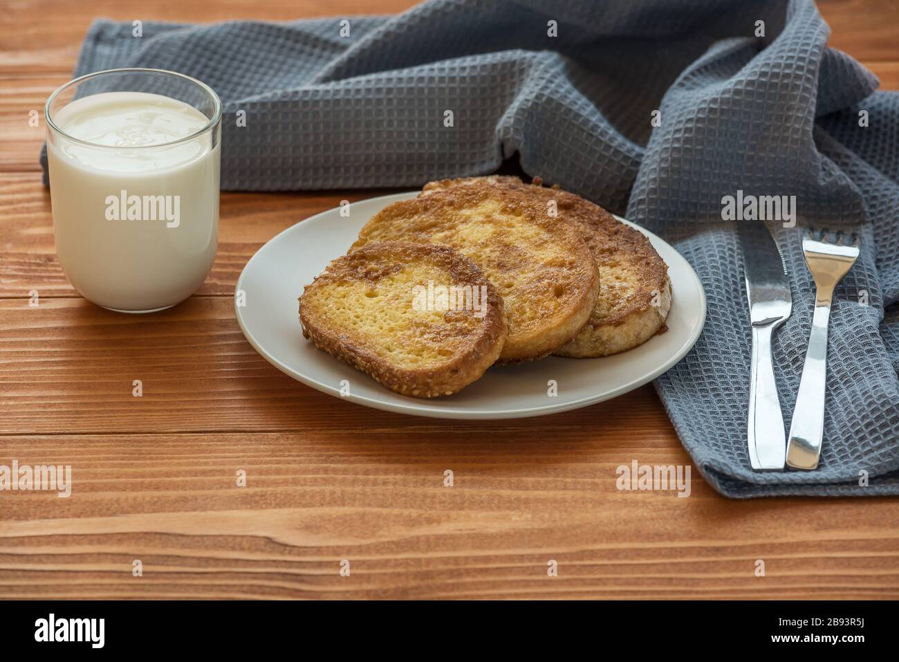 French toast - Przenice - slices of bread soaked in beaten eggs and milk and fried, with a glas of yogurt on a wooden table. Eggy bread, Bombay toast Stock Photo