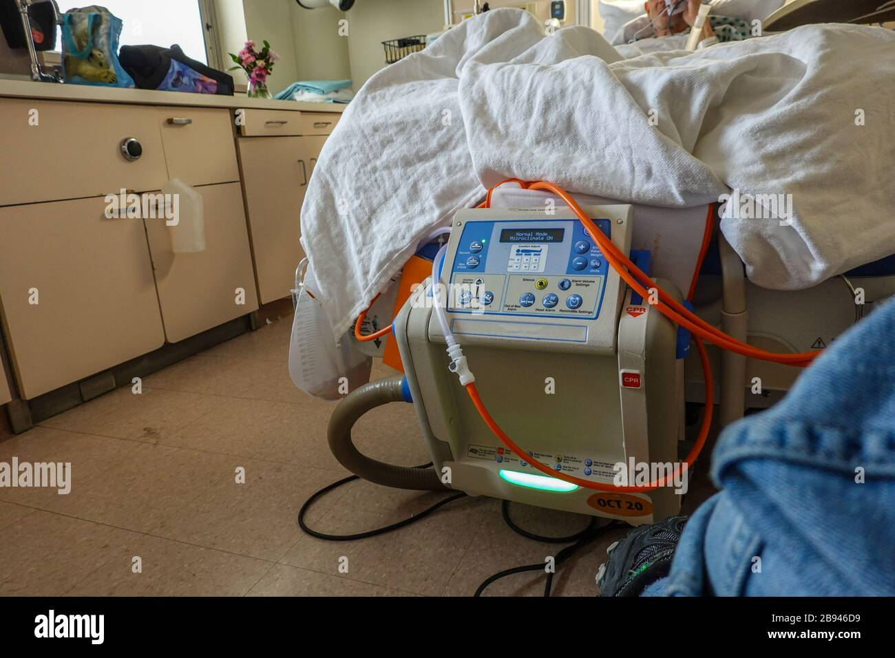 A patient seen in a hospital bed with tubes attached to a bed adjustment machine Stock Photo