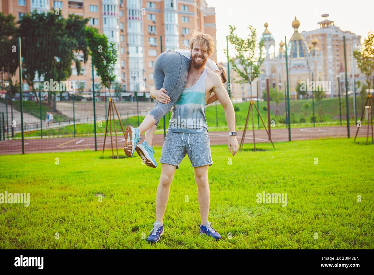 Love, fun, spott and people. Portrait of a happy young couple smiling, hugging and having fun while training. Happy athletic couple talking and Stock Photo