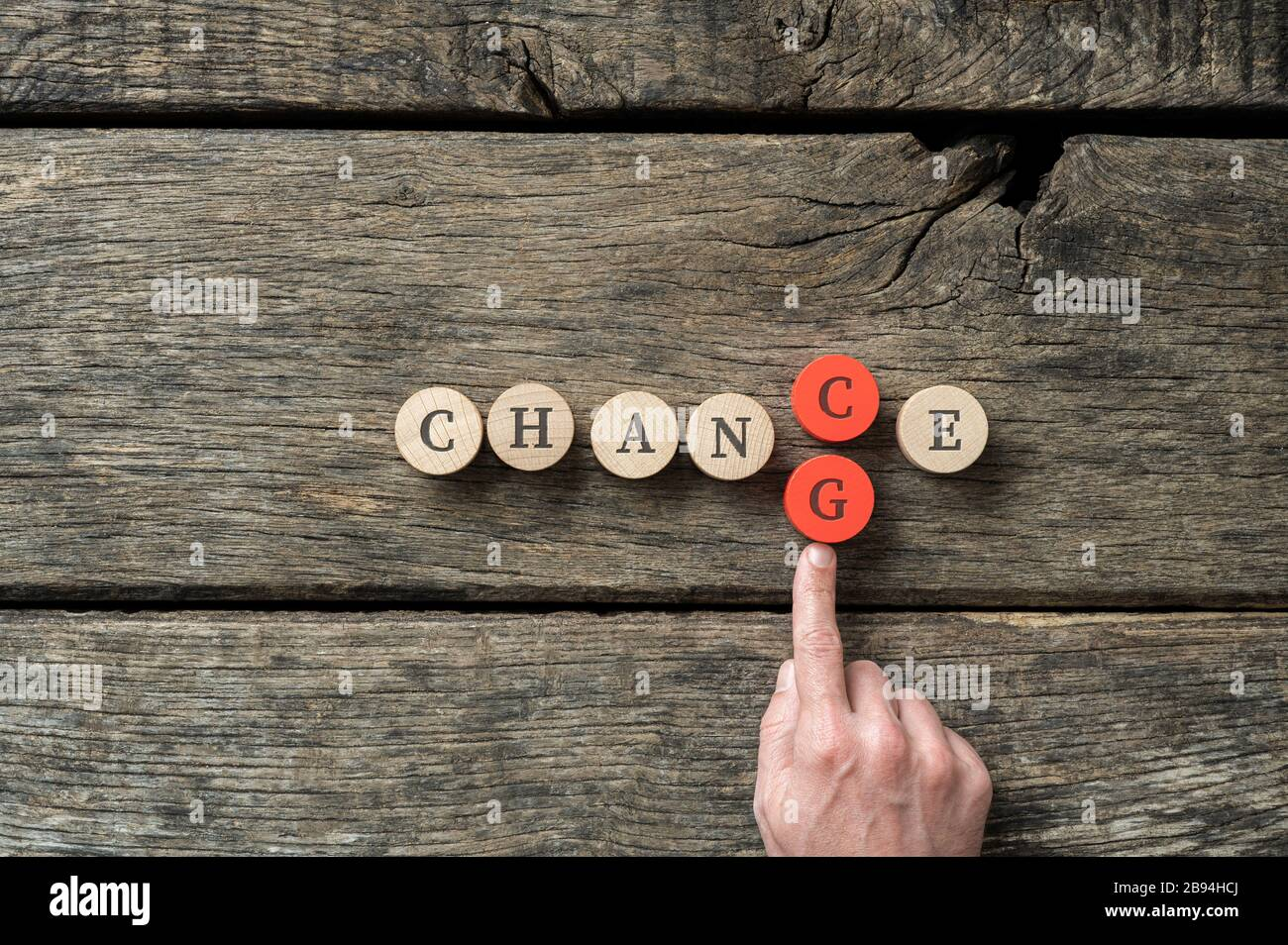 Word Chance spelled on wooden cut circles with male hand pusing in letter G to change it into Change. Stock Photo