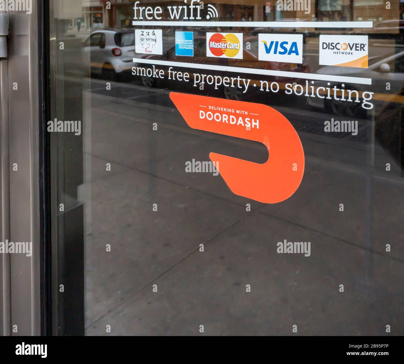 A sticker on the door of a Chick-Fil-A in New York informs shoppers of their use of Doordash as a delivery service, seen on Saturday, March 21, 2020. (© Richard B. Levine) Stock Photo