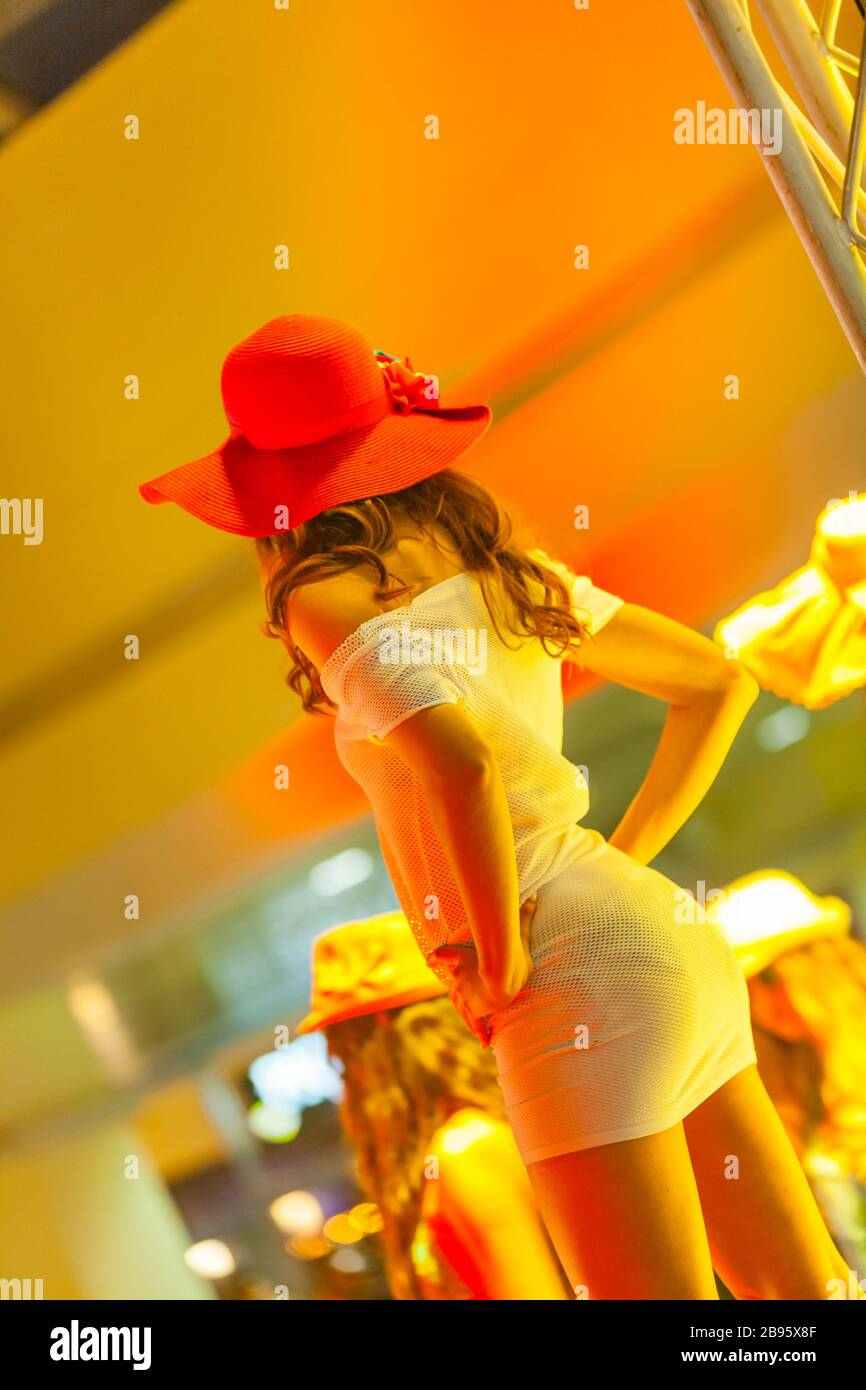 Female model on fashion runway strike striking pose posing hands on hips Stock Photo