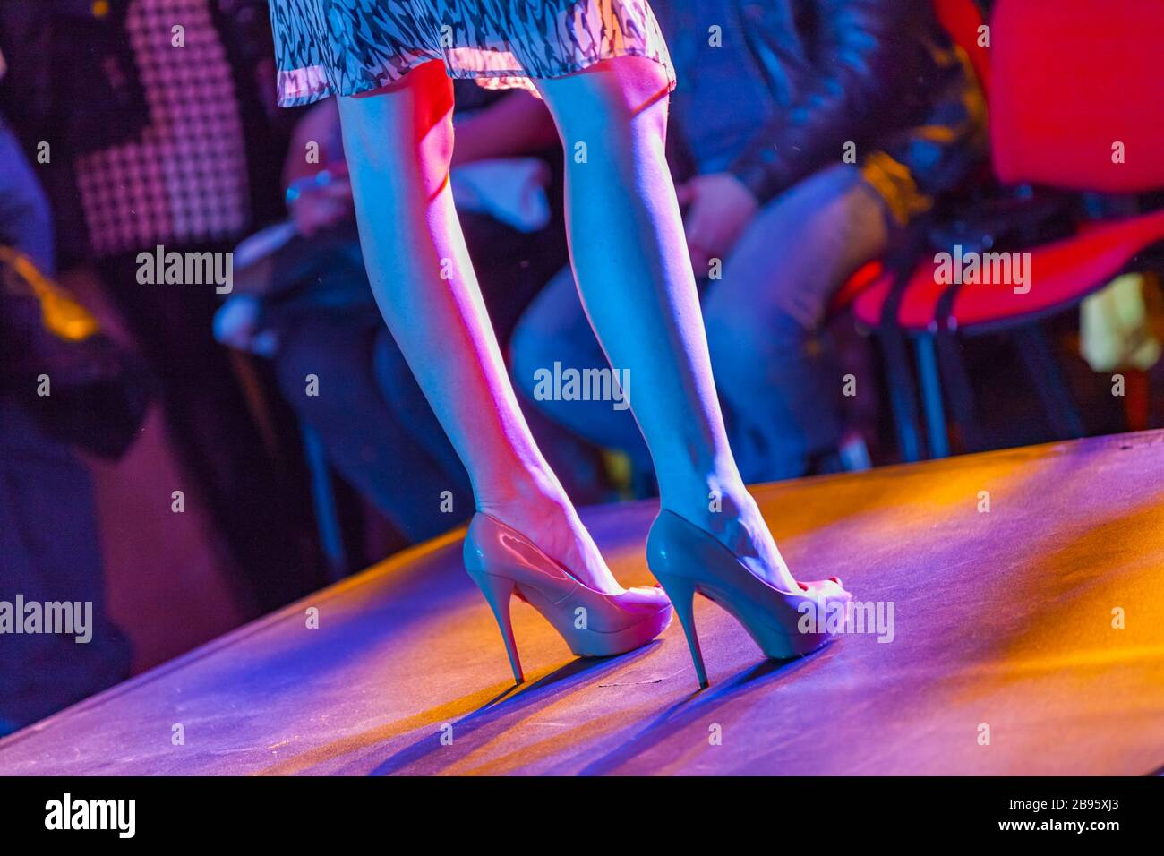Female model on fashion stage runway legs and heels standing towards public Stock Photo