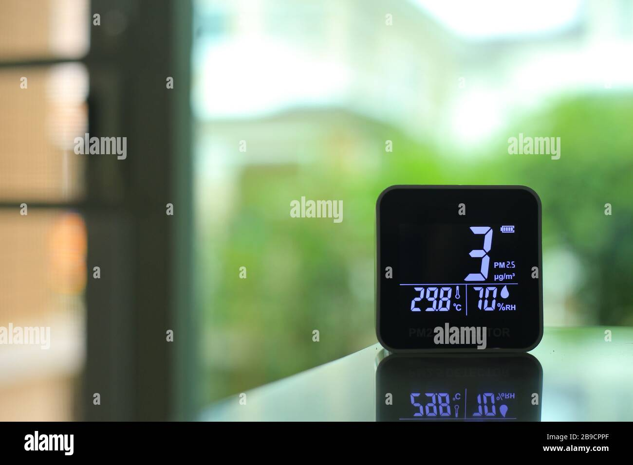 air quality sensor placing on a table indoor. sensor found small amount of air pollution of PM 2.5 the poisonous harmful particulate matter invisible Stock Photo