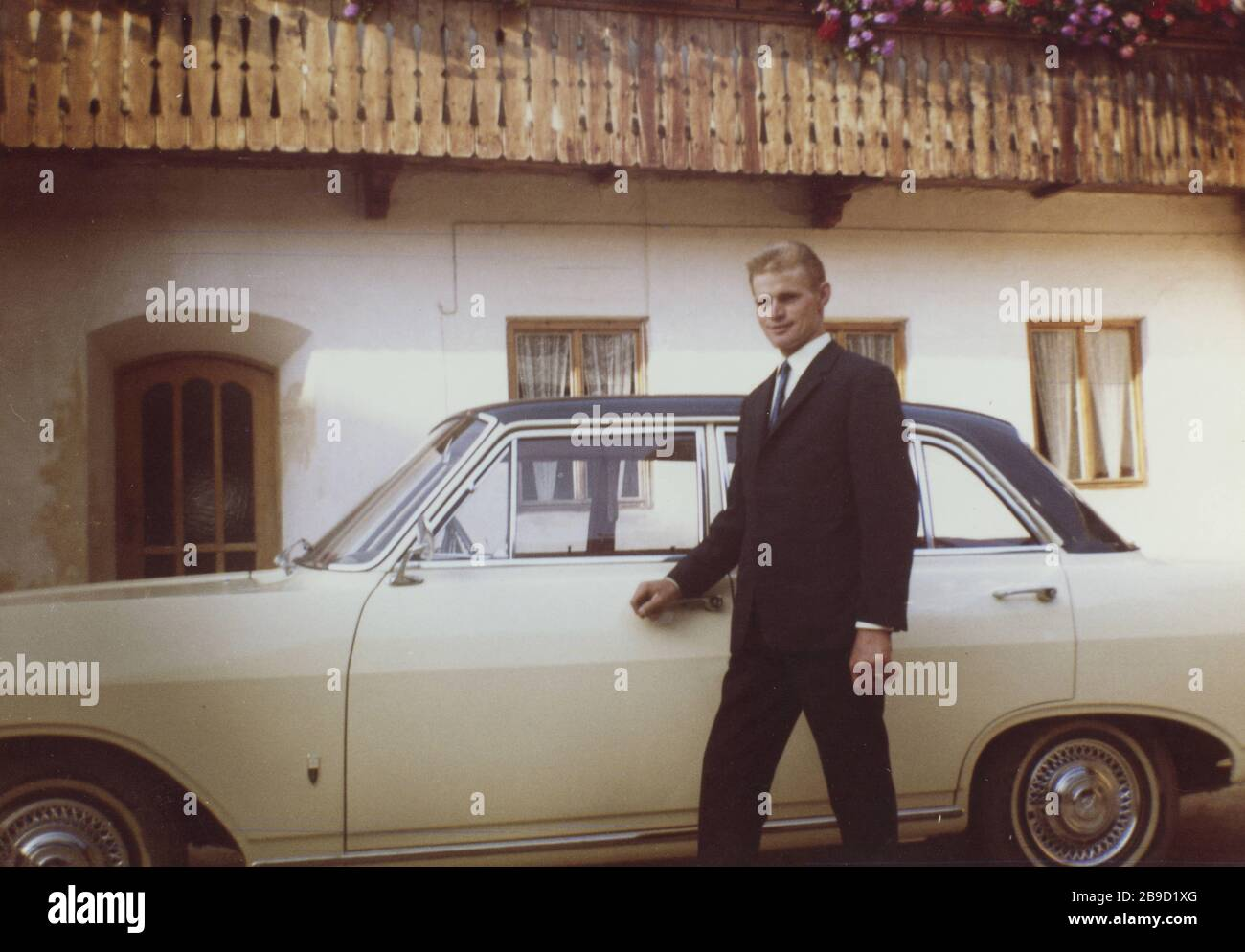 A young man in a suit poses in front of a beige car in front of an alpine style apartment building. [automated translation] Stock Photo