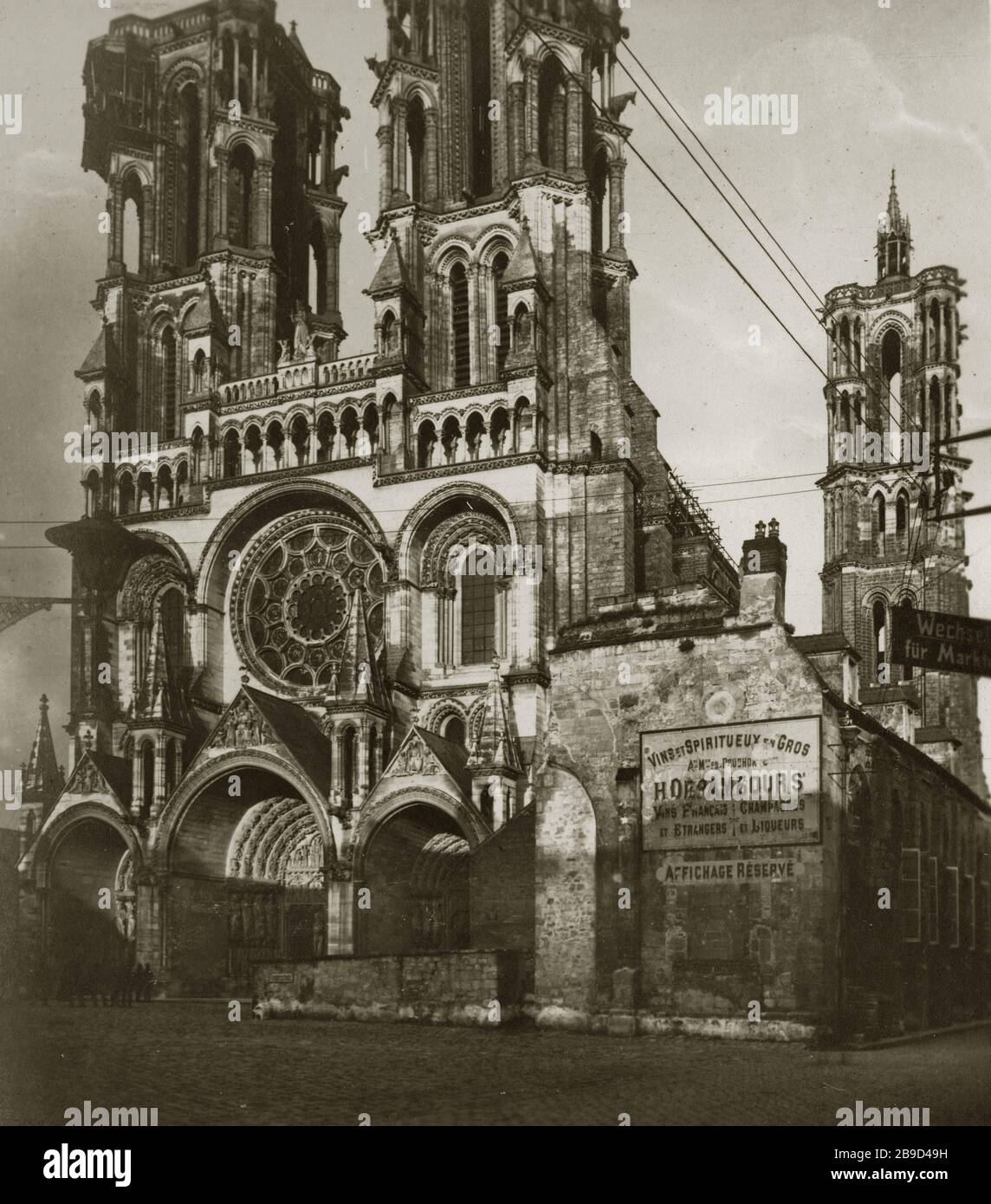 """View of the main portal of Laon Cathedral (Notre-Dame de Laon). Poster on the façade: """"Vins et Spiritueux en gros""""... [automated translation] Stock Photo"""