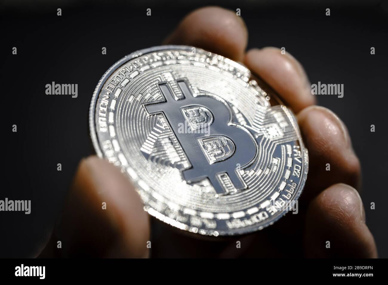 Coin with Bitcoin sign in a hand, Münze mit Bitcoin-Zeichen in einer Hand Stock Photo