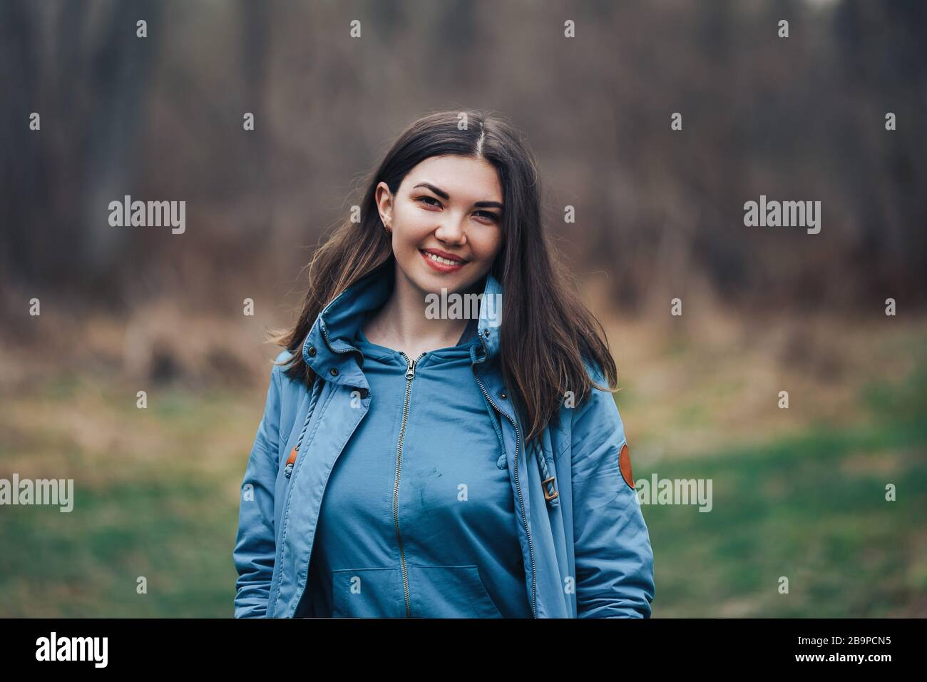 beautiful young smiling dark-haired woman in green jacket outdoor in forest Stock Photo