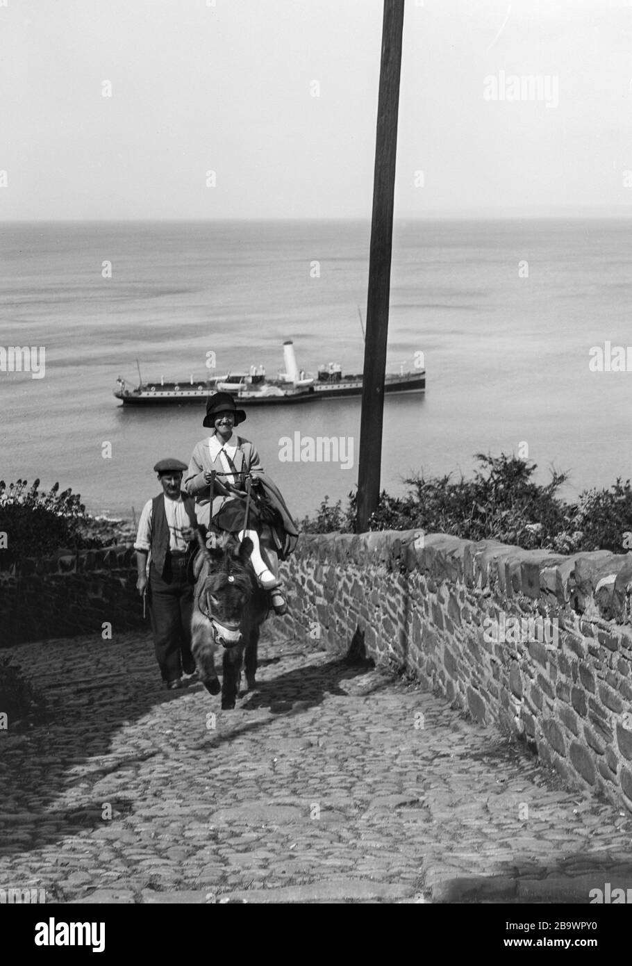 Archive image circa 1925 of a woman riding a donkey up from the beach to Clovelly village, Devon, UK, showing a steamer in the background. Scanned from the original negative. Stock Photo