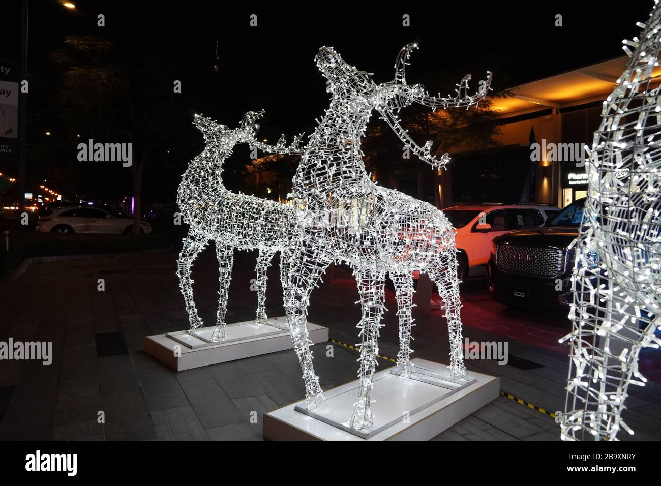 Glowing reindeer made of wire and light bulbs. Christmas decorations. Christmas Lights on reindeer shape wire frame mesh. Deer Christmas outdoor decor Stock Photo