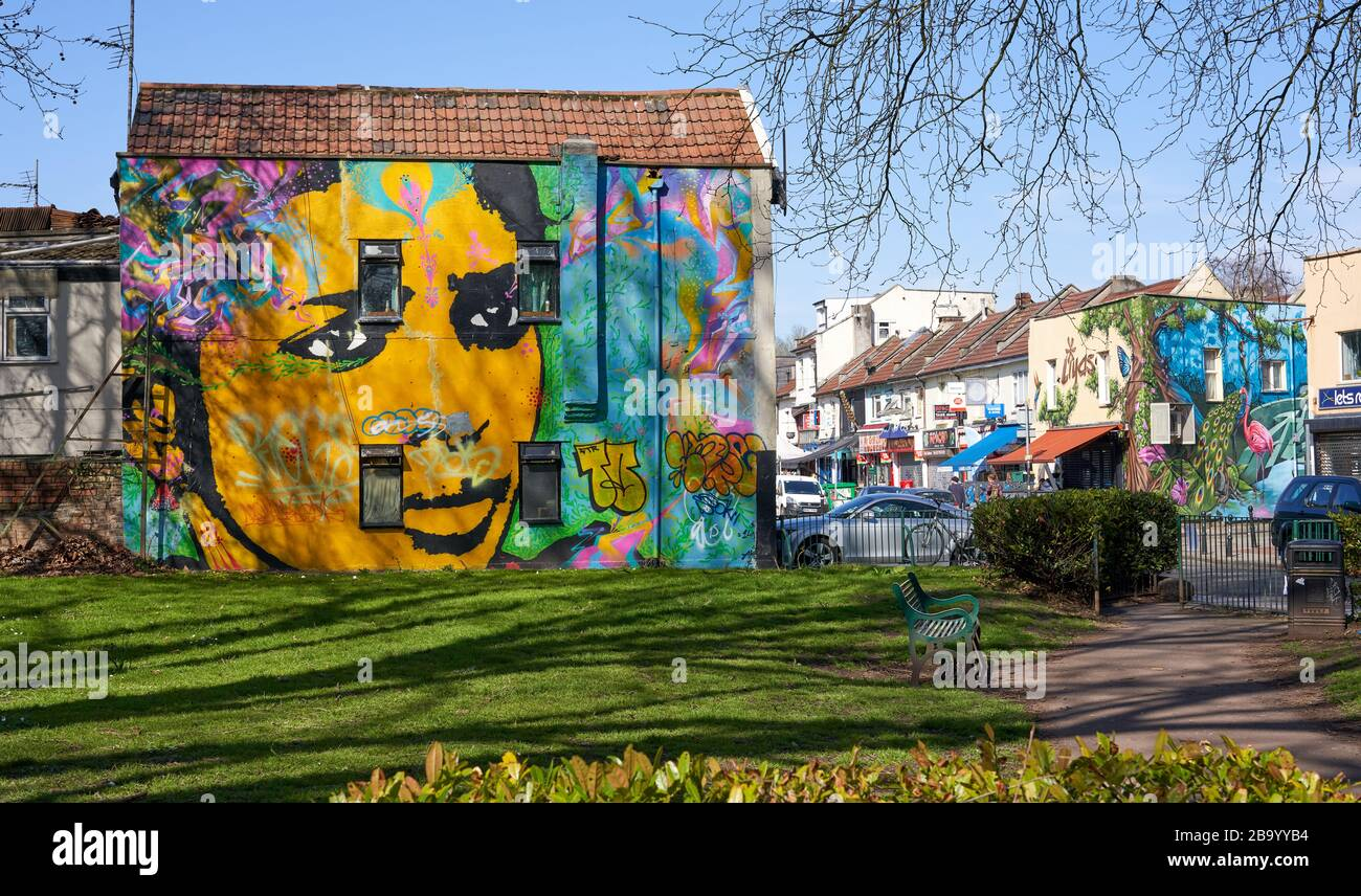 Mina Road Park in Bristol UK with mural of a woman painted on a bordering house Stock Photo