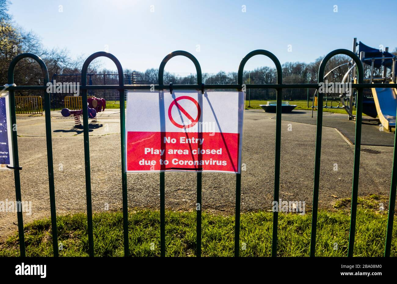Lockdown: Sign on railings of a playground for children in a park: No Entry; Play area closed due to Coronavirus: St John's Lye, Woking, Surrey Stock Photo