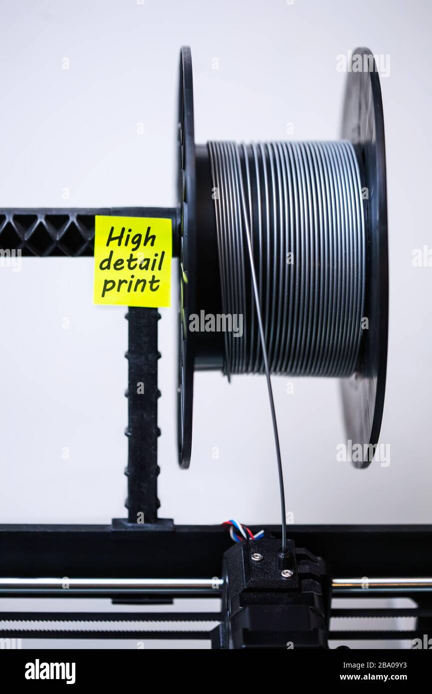 A 3d printer head with loaded filament and a spool of PLA material for high detail 3d printing. Stock Photo