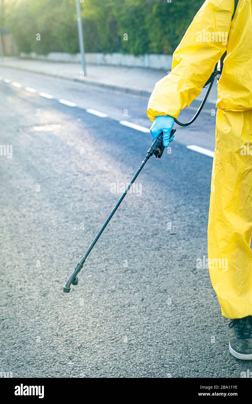 Coronavirus. A sanitation worker wearing a mask and cleaning the streets with alcohol based solution with pressure. Disinfecting against to the Corona. Stock Photo