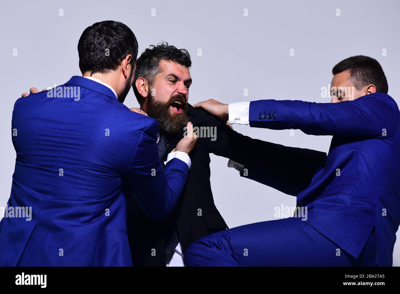 Businessmen with mad faces in formal suits on grey background. Business conflict and argument concept. Company leaders fight for business leadership. Coworkers decide upon best working position Stock Photo