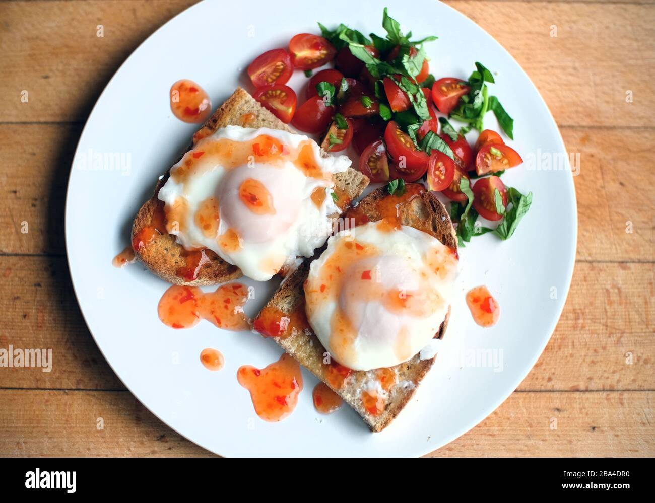 Poached eggs on toast with tomatoes, basil and sweet chilli sauce. Stock Photo