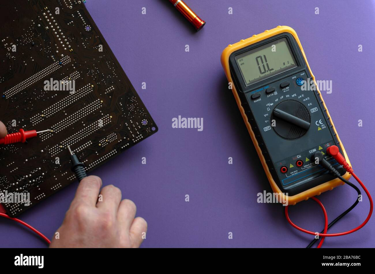 Checking the electrical resistance of the motherboard. Hands using a digital multimeter to test. View from above. Selective focus. Close-up Stock Photo