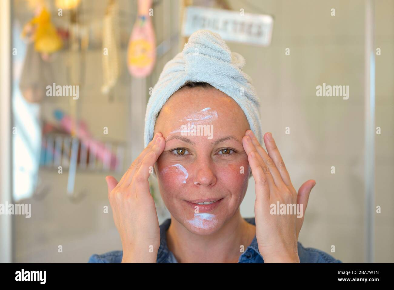Smiling woman with her hair tied up in a towel applying moisturiser to her face with her fingertips in a skin care and ageing concept Stock Photo