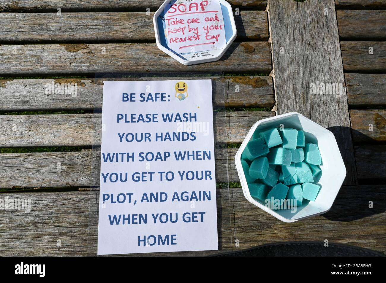 Covid19 hygiene. A container of complimentary soap with instructions to wash hands on an allotment garden during the coronavirus pandemic. Stock Photo