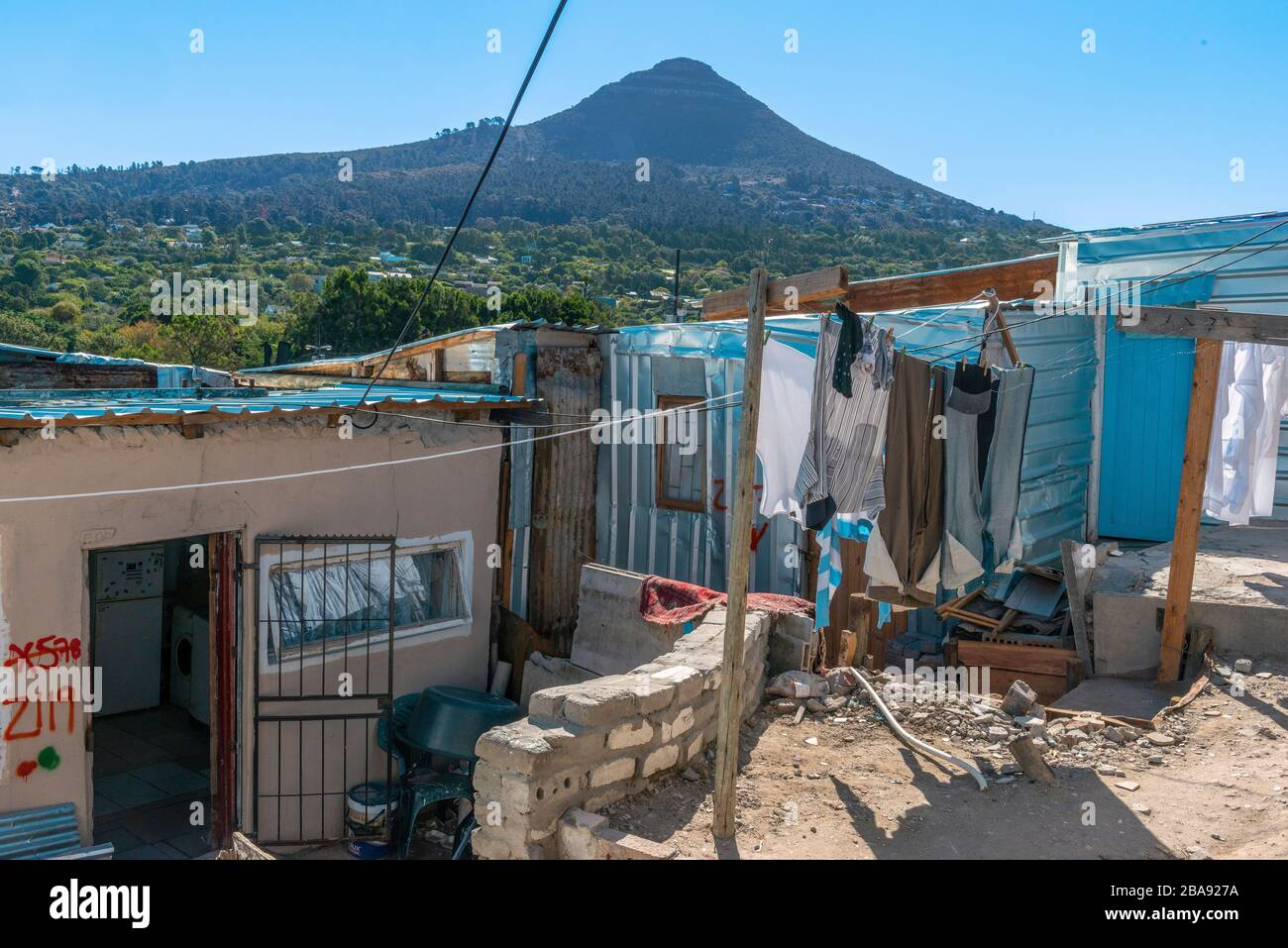 Small dwelling with washing hanging outside in the overcrowded Imizamo Yethu Township, Hout Bay, Cape Town, South Africa Stock Photo