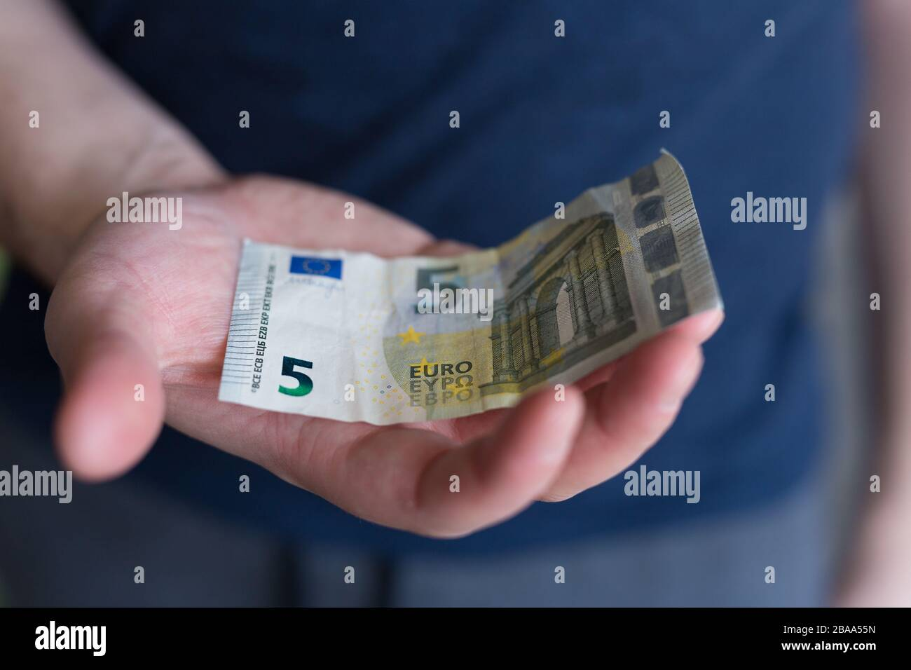 5 euro banknote. Man Hand holding cash paper money.Financial and money concept. job seeker. unemployed.  Stock Photo